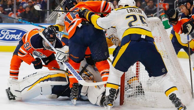 Mar 1, 2018; Edmonton, Alberta, CAN; Edmonton Oilers forward Jujhar Khaira (16) and forward Drake Caggiula (91) looks for a loose puck in front of Nashville Predators goaltender Pekka Rinne (35) during the first period at Rogers Place. Mandatory Credit: Perry Nelson-USA TODAY Sports