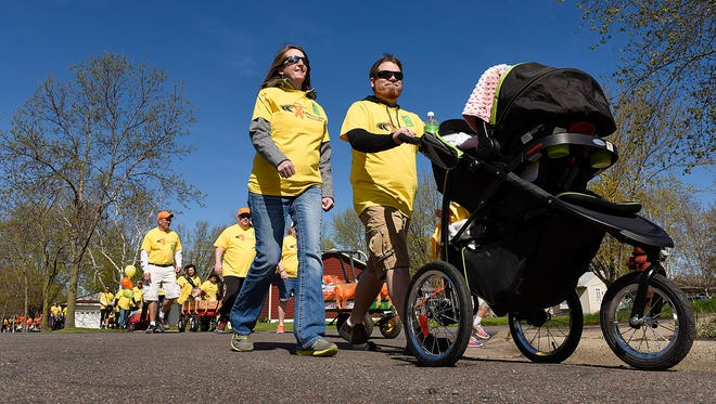 Erin and Tyler Chelgren, Buffalo, with their 5-month-old daughter Margo, take part in the Walk MS to benefit the Multiple Sclerosis Society Sunday, May 1, starting at Apollo High School.