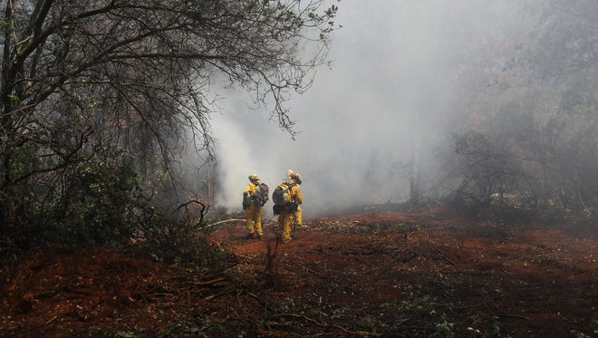 California Department of Forestry and Fire Protection firefighters work to contain a fire Tuesday afternoon off Vista Pine Lane in north Redding.
