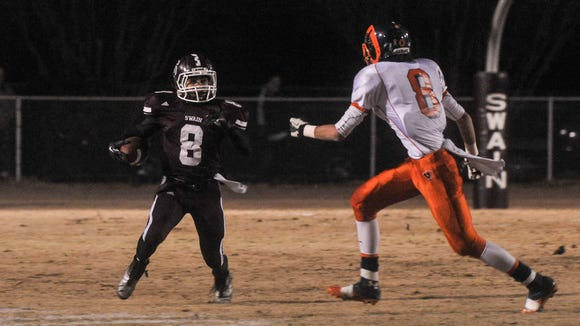 Swain County's Kobe Toineeta, left, runs with the ball during last year's 1-AA state playoff win over Starmount.