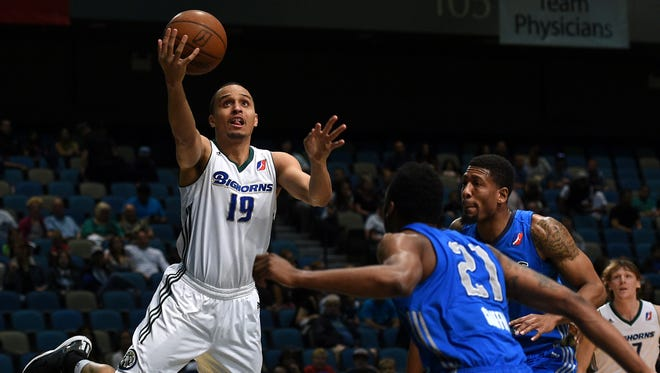 Reno Bighorns' Reggie Hearn drives against the Texas Legends' Eric Griffin (21) at the Reno Events Center in Reno, Nev. on March 28, 2015.