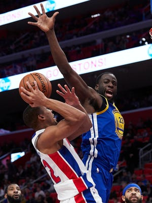 Dec 8, 2017; Detroit, MI, USA; Pistons guard Avery Bradley shoots against Warriors forward Draymond Green in the second half at Little Caesars Arena.