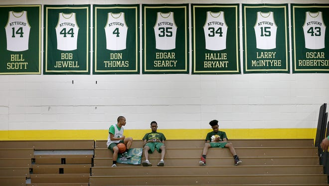 Crispus Attucks Tigers Dayon Coe (21),left, Derrick Briscoe (11) and Zac Townsend (33) hang our below the jerseys of the 1959 Attucks team  following their practice Tuesday, March 21, 2017, afternoon at Crispus Attucks High School. The Tigers are preparing for the 3A Indiana State finals game against the Twin Lakes Indians.