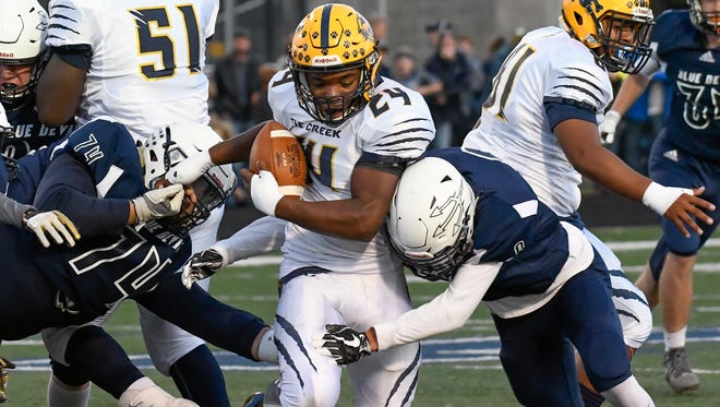 Gull Lake defenders get a stop on Battle Creek RB Tyshaan Williams (24) during game action Friday night.
