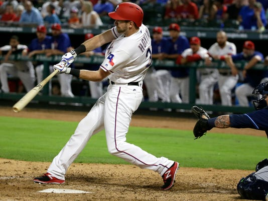 Texas Rangers Jared Hoying hits an BRI single in front of Tampa Bay Rays catcher Jesus Sucre during the eighth inning of a baseball game in Arlington,Texas, Tuesday, May 30, 2017. Rangers Pete Kozma scored on the play and the Rangers won 9-5. (AP Photo/LM Otero)