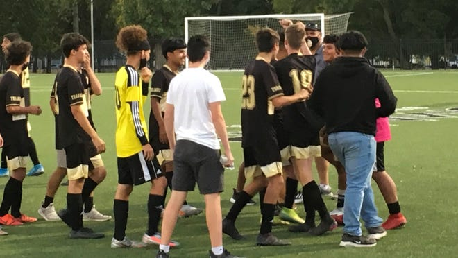 Topeka High sophomore Aidan Morrison (19) is mobbed by his teammates after scoring the game-winning goal in the Trojans' 3-2 overtime decision over Topeka West.