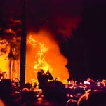 MSU fans watch a fire fueled by a couch and other debris just outside of a Cedar Village apartment buildings after the MSU football teams' win over Ohio State in the Big Ten Championship game Dec. 8, 2013 in East Lansing.