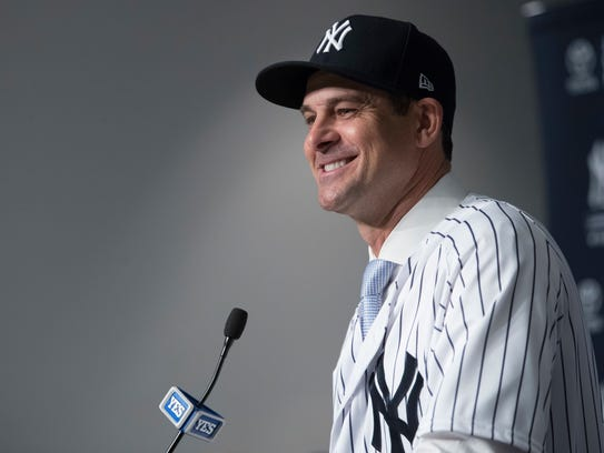 Yankees manager Aaron Boone smiling as he speaks to reporters during his inaugural news conference.