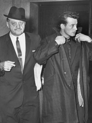 "Bank robber Morris Johnson (right) leaves court, Feb. 1, 1963. With him is his attorney William Erbecker. Johnson's FBI's Most Wanted List poster described his eyes as ""blue (unusually vivid blue)."""