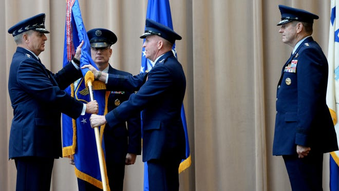 """The change of command is an official ceremony where the command flag is exchanged, representing the responsibility and authority being transferred from one officer to another. At Barksdale Air Force Base Tuesday, Lt. Gen. Stephen W. """"Seve"""" Wilson (center) hands the Air Force Global Strike Command flag over to Air Force Chief of Staff Gen. Mark Welsh as Gen. Robin Rand (right) waits to receive it."""