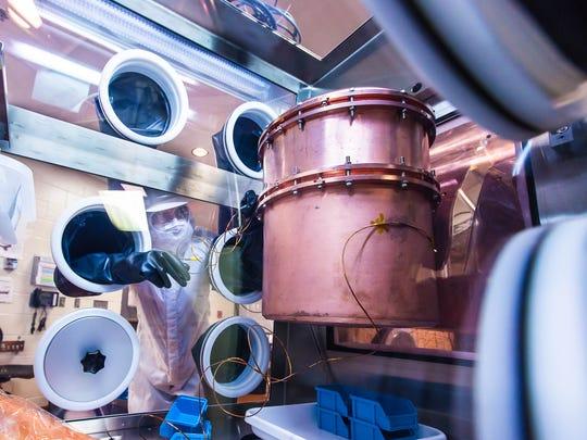 A worker builds strings of germanium detectors, held