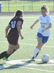 Mountain Home's Bailey Womack (14) runs past a defender