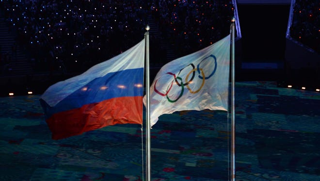 The Russian and Olympic flags are raised during the closing ceremony for the 2014 Sochi Olympic Winter Games.