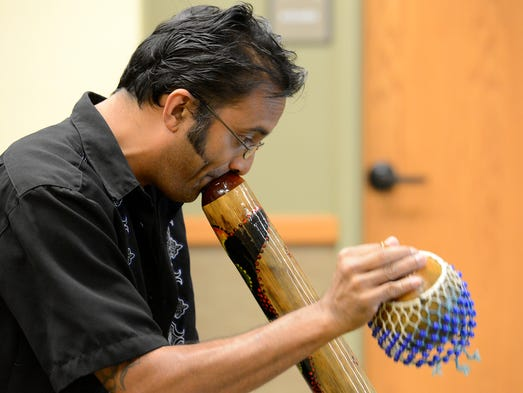 Raihan Alam, of St. Petersburg, Fla., plays a didgeridoo Saturday at the Donald W. Reynolds Library. The program, Didgeridoo Down Under, was part of the library's ongoing summer program series for kids.