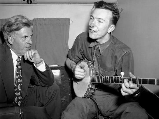 In this Aug. 28, 1948, file photo, Henry A. Wallace, left, Progressive Party presidential candidate, listens to Pete Seeger on a plane between Norfolk and Richmond, Va. The Federal Bureau of Investigation released more than 1,700 pages of documents about Seeger after the folk singer died at age 94, in January 2014.
