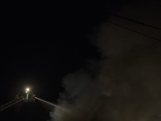 Firefighters try to control a 15-alarm fire from a