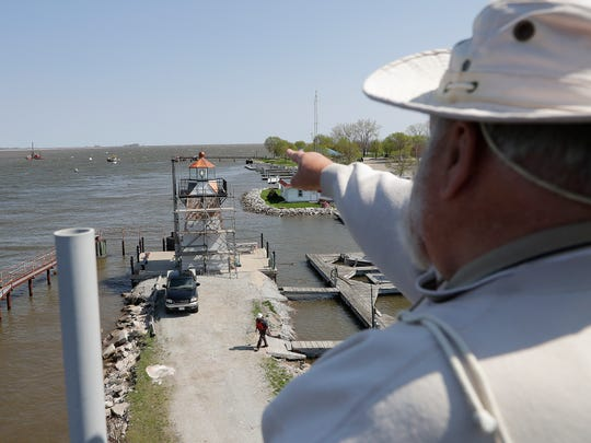 Wayne Dunbar looks toward the mouth of the Fox River pointing out the original Grassy Island site of the range lights from the top of the south Grassy Island Range Lighthouse at the Green Bay Yachting Club Tuesday, May 15, 2018 in Green Bay, Wis