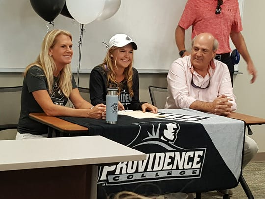 Community School senior Katie Markham (center) signed