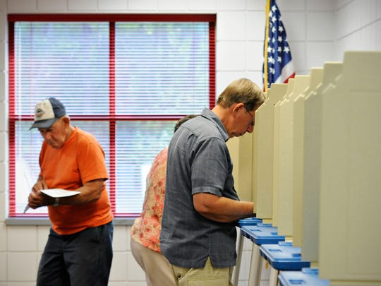 Voters complete their ballots in the primary election
