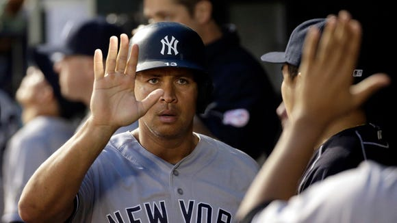 New York Yankees' Alex Rodriguez high-fives teammates in the dugout after scoring on a sacrifice groundout by Didi Gregorius in the fourth inning of a baseball game against the Baltimore Orioles in Baltimore, Saturday, June 4, 2016.