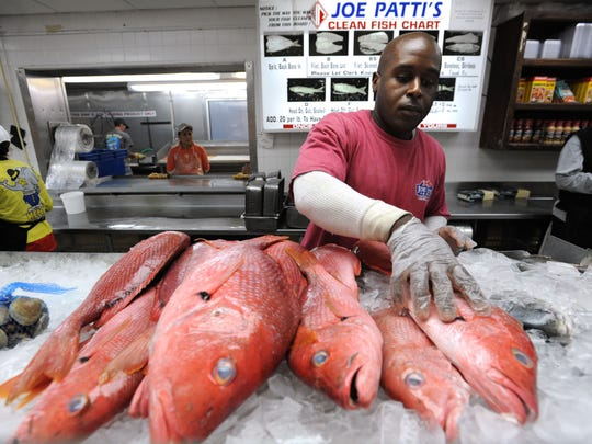 "Joe Patti's Seafood employee Terrance Williams stocks a display cooler with red snapper. The iconic fish market was named to the ""Taste 50"" by Taste of the South magazine."