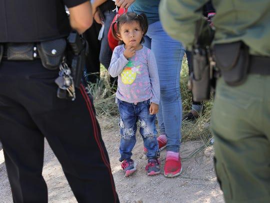 Una niña inmigrante observa a unos oficiales de inmigración mientras interrogan a sus padres.