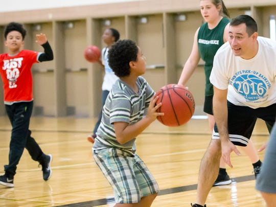 Brandon Ansell of the Oshkosh Police Department faces off with Jaymeson Towns during the Kids and Cops Basketball Game at Albee Hall on Sunday, October 2, 2016.