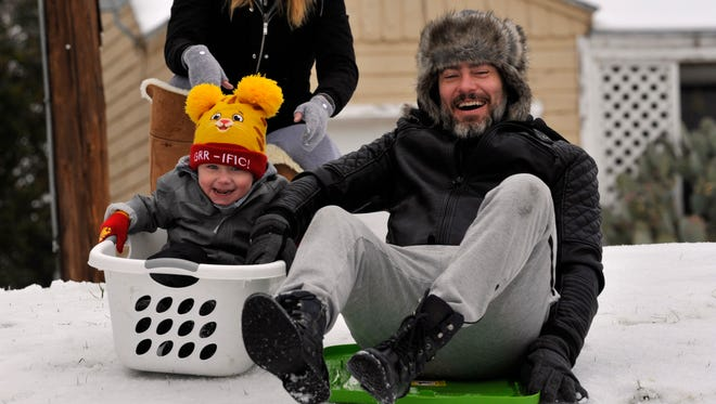 Nate and Loren Whitsett took their 2 year-old son Leo tobogganing at C.W. Gill Park on South Willis Street Thursday, using a laundry basket and a plastic bin cover as their sleds.