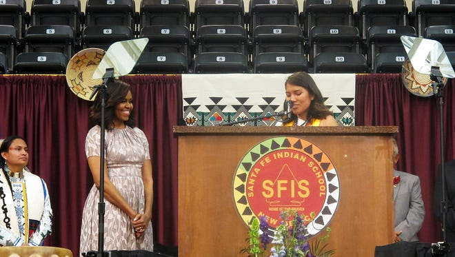 First lady Michelle Obama, left, listens as Santa Fe Indian School students prepare to present her a blanket for delivering the commencement address for their graduation on Thursday, May 26, 2016, in Santa Fe, N.M.