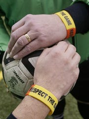 Whenever and wherever Mario D'Agostino and Kevin Winningham go to officiate soccer games, they wear these wristbands to honor the memory of friend and fellow referee John Bieniewicz.