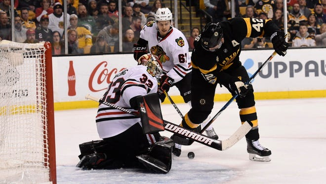 Bruins forward David Backes (42) battles for a rebound in front of Blackhawks goalie Scott Darling (33) during the second period.