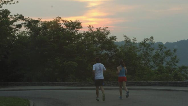 A couple runs around the overlook at Eden Park at sunrise Wednesday.