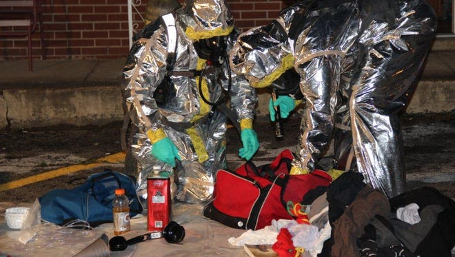 Agents collect pieces of a meth lab found at a motel on Providence Boulevard early Wednesday morning.