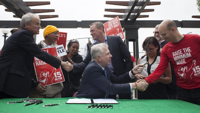 Seattle Mayor Ed Murray, center, celebrates Tuesday after signing a bill that raises the city's minimum wage to $15 an hour.