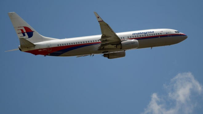 """A file photo taken on March 18, 2013 shows a Malaysia Airlines Boeing 737 plane flying over the Sukarno-Hatta airport in Tangerang. Malaysia Airlines said on July 17, 2014 that it had """"lost contact"""" with one of its passenger planes whose last known position was over Ukraine."""