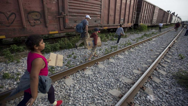 Migrants get off a train in Mexico and head for the U.S. border July 12.
