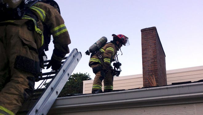Firefighters attend to a chimney fire on Aumsville Highway Monday morning.