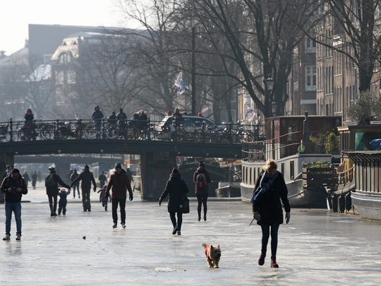 People walk and skate on the frozen Prinsengracht canal