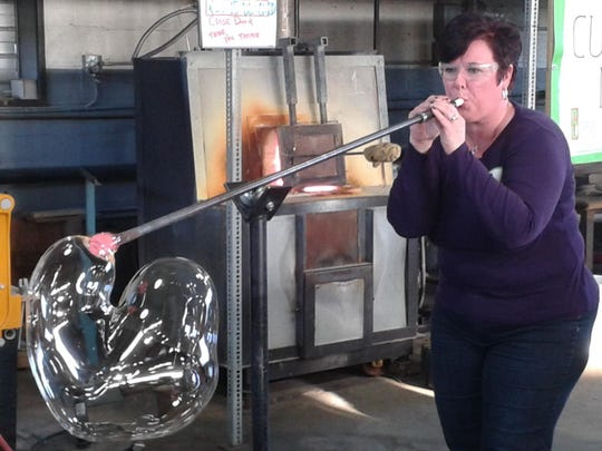 Jenai Close of Dearborn makes a glass bubble before trying her hand at reed-making.