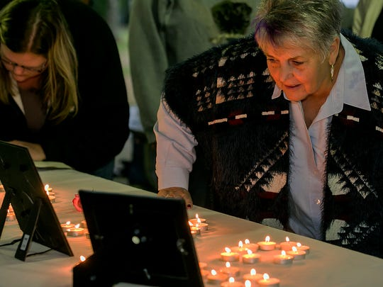 Suzanne Videon, mother of missing teen China Videon, looks at photos and the memorial in honor of China Videon before the start of Monday's candlelight vigil at Barfield Crescent Park.