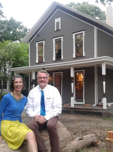 """Julie and Phil Ostrem relax after their """"day jobs"""" on a downed log in front of the nearly completed restoration of their 1890 Summit Street home in Iowa City.  The couple live downstairs and are preparing to rent out their two modern apartments on the second floor. Landscaping the overgrown lot is the final step of this extensive renovation project."""