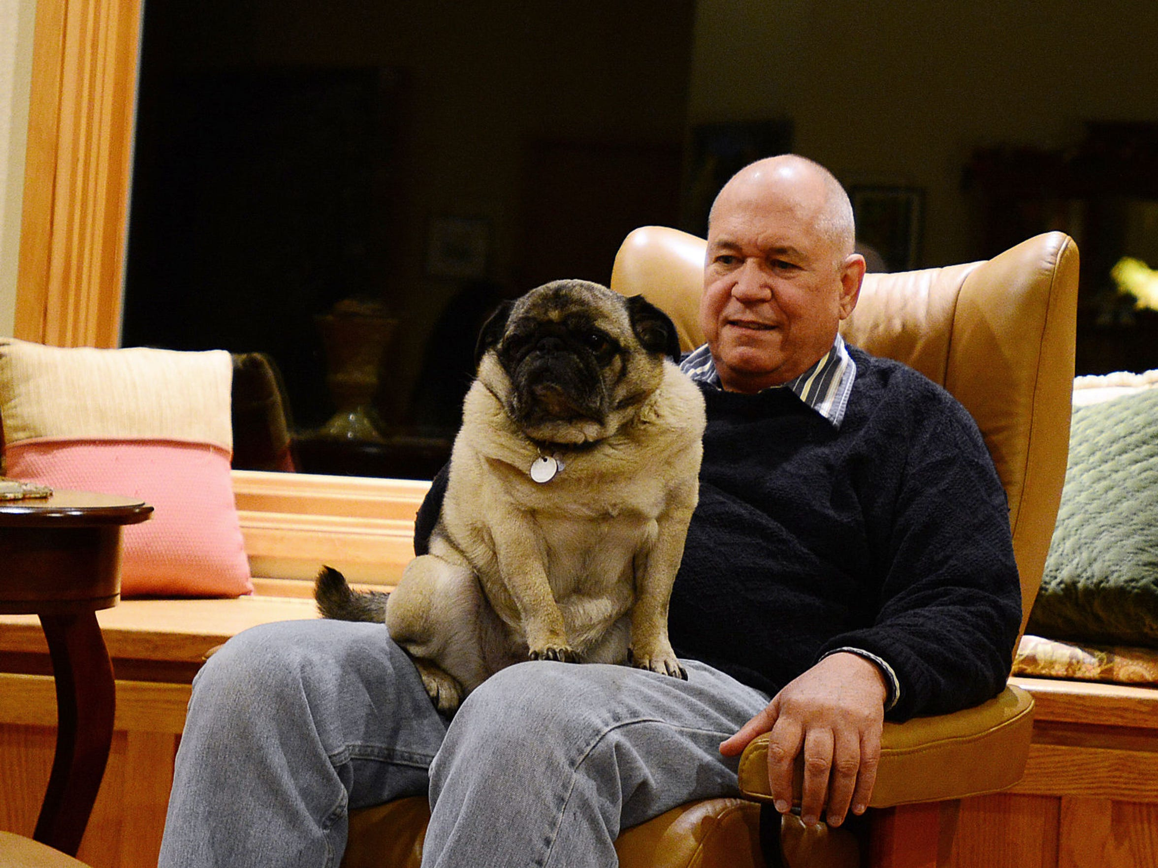 Dr. Peter Rasmussen sits with his dog, Pugsley, at