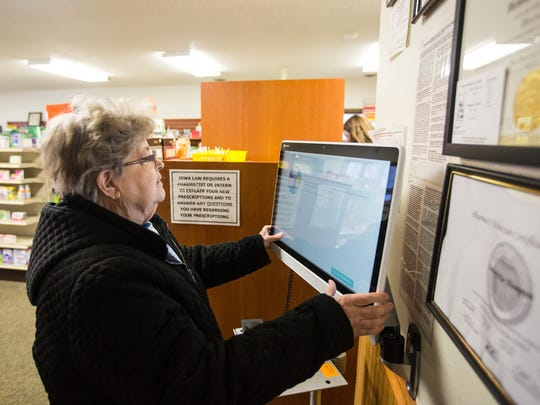Dorothy Perish, 85, uses a tablet computer to fill a prescription at the NuCara Pharmacy in Zearing Thursday, Feb. 25, 2016.