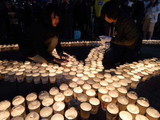 High school students light some 3,000 candles to pray