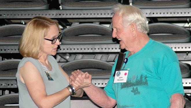 "Second annual Elder Care Symposium keynote speaker Beth Nolan, Ph.D. demonstrates the ""Hand-under-Hand"" technique with attendee volunteer John Reckard."