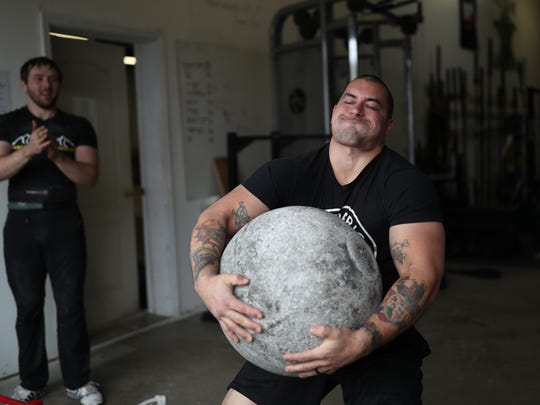 Kyle Rojas lifts a 240 pound stone as a part of his training with the Barbaric Barbell Strongman Team as fellow weight lifter Brett Fain watches at Tallahassee Strength Club at Boot Camp Fitness and Training on Feb. 2.