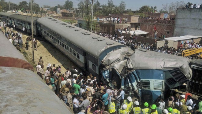 Indian rescue workers gather at the site of a train accident near Bachhrawan village in Uttar Pradesh state, India, on March 20.