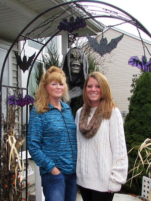 Ann Slowik, left, of Horseheads, her daughter Alyssa and some of their closest friends stand at the entrance to Slowik's Belwood Drive home, which is decked out for Halloween.