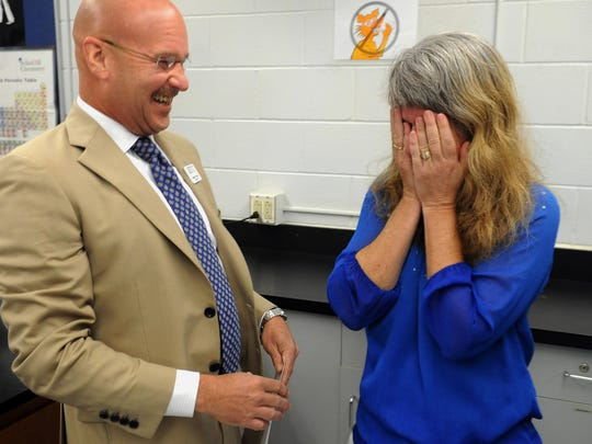 Dunbar High School teacher Laurie Metz covers her face while being told that she is one of the finalists for the Golden Apple Teacher of The Year, by Marshall Bower of the Foundation for Lee County Public Schools.