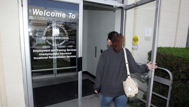A woman walks into the New Jersey One-Stop Career Center in Neptune in 2011. The state's unemployment fund is fully solvent again, Gov. Chris Christie announced Tuesday.